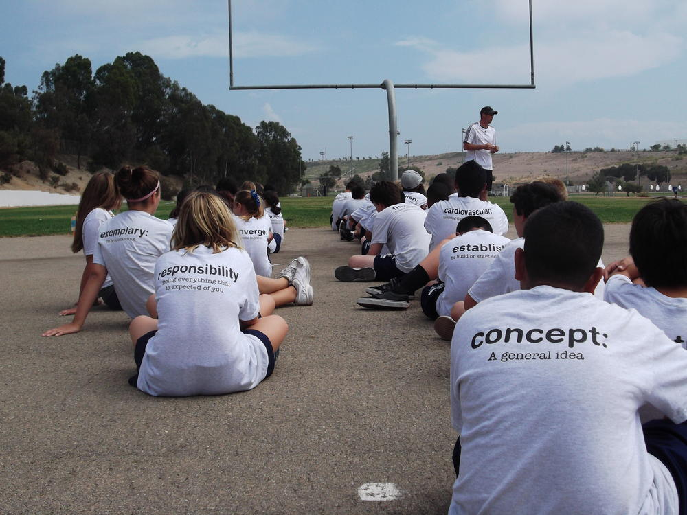 Students sitting on blacktop in PE class